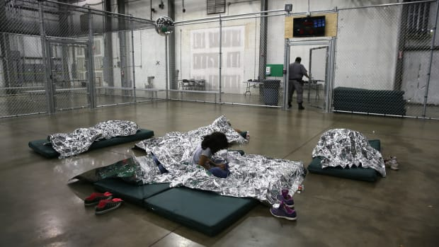 A girl from Central America rests on thermal blankets at a detention facility run by the U.S. Border Patrol on September 8th, 2014, in McAllen, Texas.