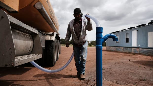 Cecil Joe, a member of the Navajo Nation, fills a water tank supplying one Navajo household on June 5th, 2019, in Thoreau, New Mexico. Due to a legacy of poverty, marginalization, and disputed water rights, up to 40 percent of Navajo families don't have clean running water at home and are forced to rely on visits to water pumps.