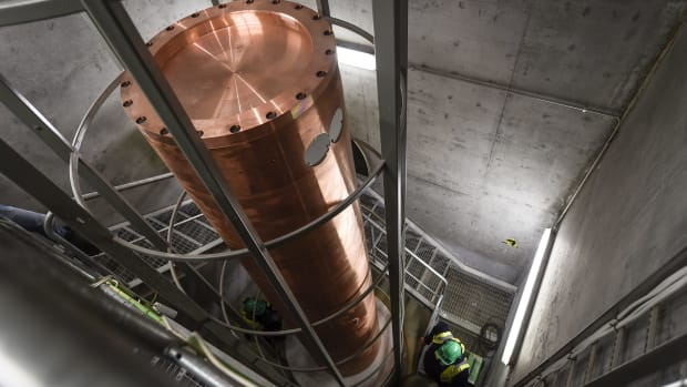 A copper canister for high-level nuclear waste is lowered into one of many storage chambers at Onkalo.