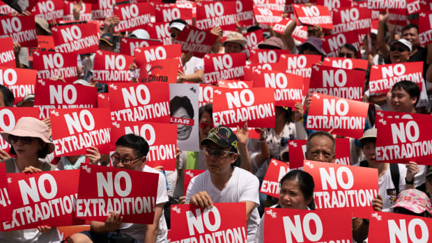 Protesters hold placards and shout slogans during a rally against the extradition law proposal on June 9, 2019, in Hong Kong.