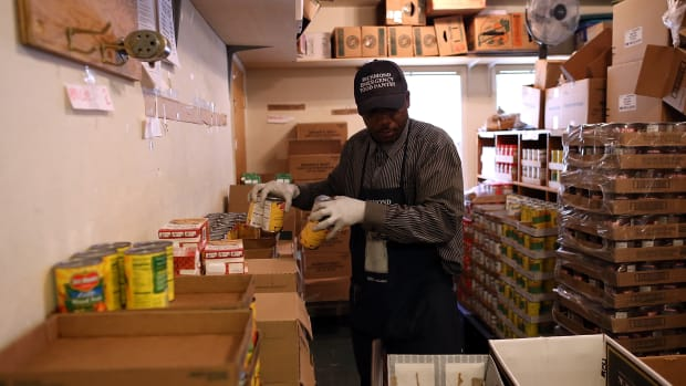 Richmond Emergency Food Bank volunteer Abdul Olorode packs boxes with food to be handed out to needy people on November 1st, 2013, in Richmond, California.