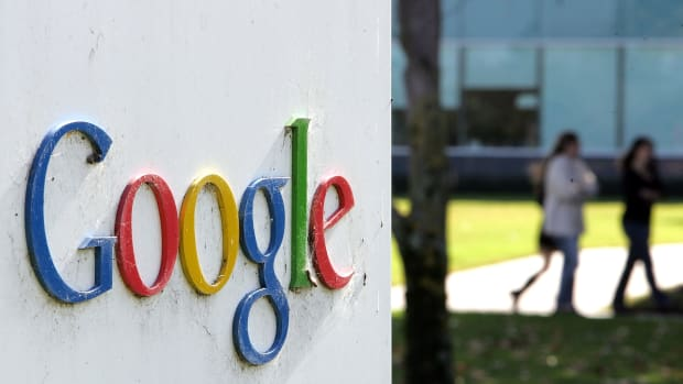 People walk near a sign outside of Google headquarters.