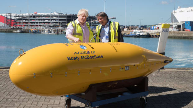 Boris Johnson (L) stands next to Boaty McBoatface, an autonomous underwater vehicle.