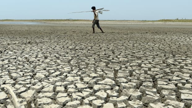 An Indian man walks over the parched bed of a reservoir on the outskirts of Chennai on May 17th, 2017.