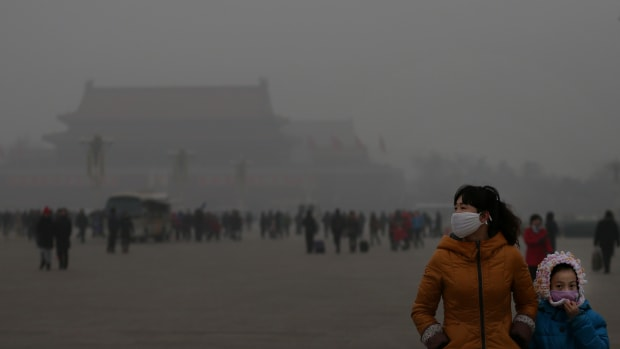 A tourist and her daughter wearing masks visit Tiananmen Square at dangerous levels of air pollution on January 23rd, 2013, in Beijing, China.