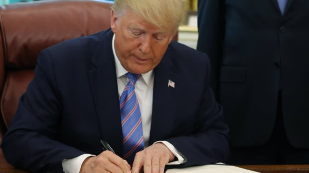 President Donald Trump signs documents.
