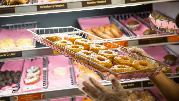 A Dunkin' employee places a fresh tray of doughnuts on the shelf in New York City.