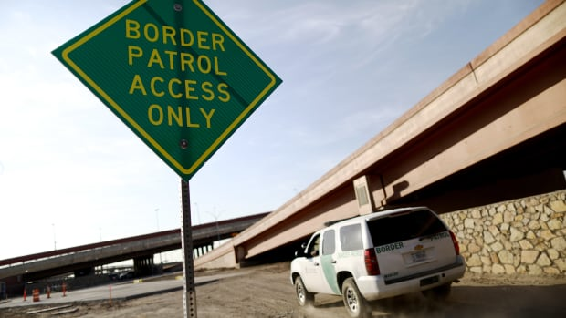 A U.S. Border Patrol vehicle passes a Border Patrol Access Only sign near the U.S.–Mexico border.