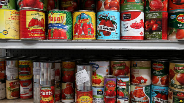 Canned tomatoes line the shelves of a food pantry.