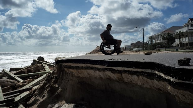 Bug Mohani steers his wheelchair along a part of a highway washed out by Hurricane Matthew in Flagler Beach, Florida, on October 9th, 2016.