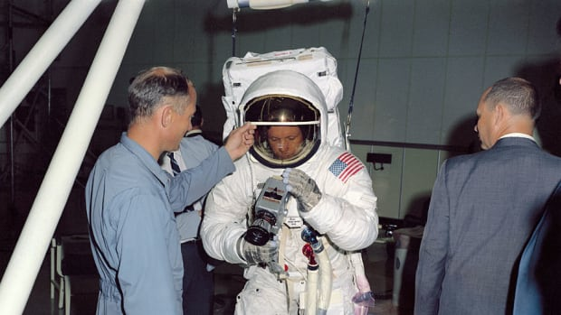 During training, Neil Armstrong practices attaching a Hasselblad camera to a mount on his suit. Buzz Aldrin helps him see what he's doing by raising his visor.