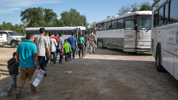 Immigrants walk to U.S. Homeland Security buses to be transferred to a U.S. Border Patrol facility in McAllen after crossing from Mexico on July 2nd, 2019, in Los Ebanos, Texas.