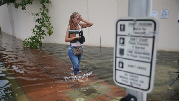 A woman walks through a flooded street that was caused by high tides and sea level rise due to climate change on September 29th, 2015, in Miami Beach, Florida.