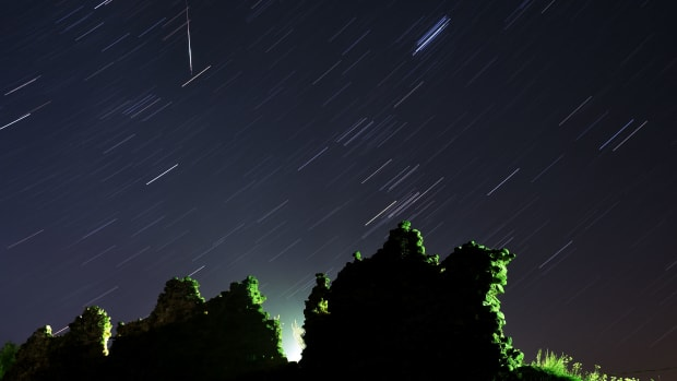 A long exposure picture of a Perseid meteor crossing the night sky and stars trails.