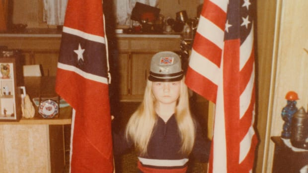 A young Jvonne Hubbard poses with American and Confederate flags.