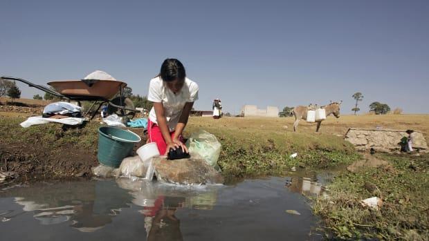 A Mexican Mazahua girl washes some clothes at La Presita reservoir in Loma de Juarez, Mexico.