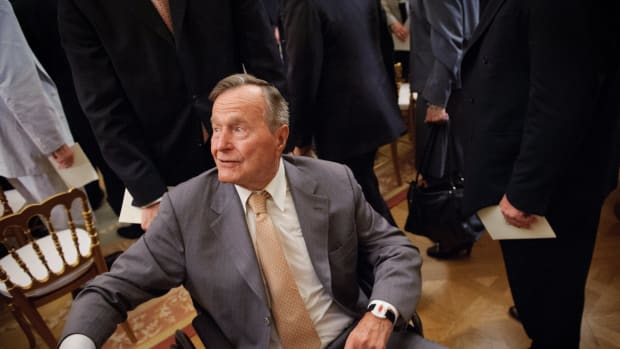 Former President George H.W. Bush shakes hands as he departs from the East Room of the White House following the official portrait unveiling of his son, former President George W. Bush, on May 31st, 2012, in Washington, D.C.