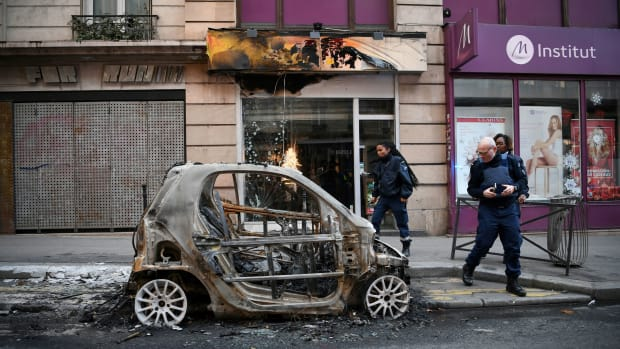 "Police look at a burnt car in Paris, France, on December 9th, 2018—one day after ""yellow vest"" protests rocked the country. More than 1,700 people were arrested across France during the latest ""yellow vest"" protests against rising living costs."