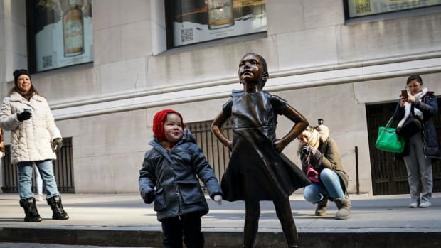 A child stands alongside the Fearless Girl after a ceremony unveiling the statue's new permanent location outside the New York Stock Exchange on December 10th, 2018. The bronze statue, symbolizing female empowerment, has been moved from its Wall Street home opposite the Charging Bull statue in New York City.