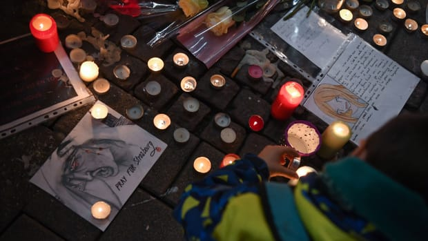 A man lights candles at a vigil on December 13th, 2018, in memory of the victims of an attack near the Christmas market of Strasbourg in France. Officials say three people were killed and 13 wounded when a lone gunman, identified as Cherif Chekatt, 29, opened fire on shoppers on December 11th.