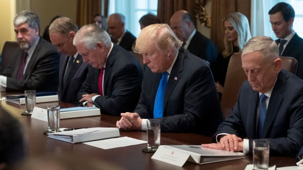 President Donald Trump bows his head during a prayer at a cabinet meeting in the White House in Washington, D.C., on December 20th, 2017.