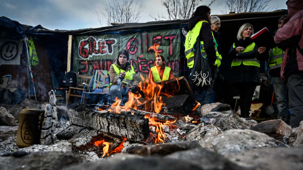 """Yellow vest"" protesters occupy a traffic circle on December 11th, 2018, in Saint-Etienne, France. Although the president offered a financial relief package to quell the revolt, some demonstrators said they were not ready to call a halt to the protests."