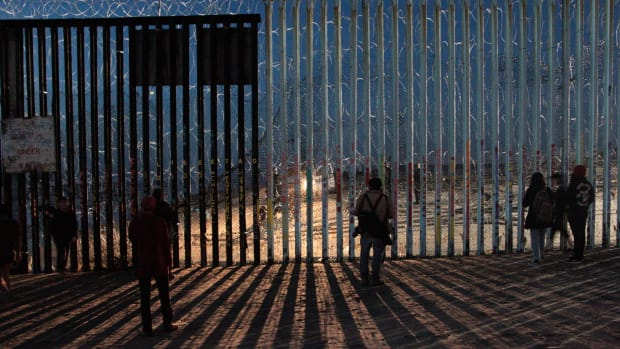 Border Patrol agents shine a light through the border wall as migrants search for a way to cross.