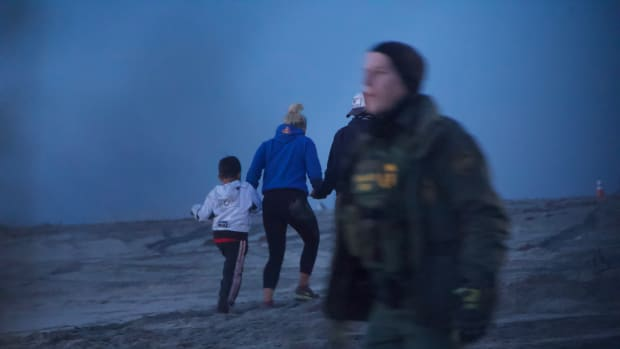 A family of three from Honduras crosses the border wall on the beach in Tijuana, Mexico, before surrendering to Border Patrol on the other side on December 13th, 2018.