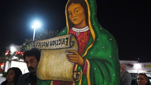 Residents facing eviction from their homes stage a protest led by a statue of the Virgin de Guadalupe holding an eviction scroll.