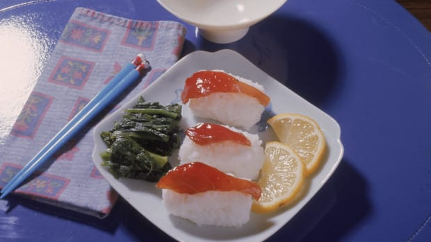 Photograph shows a plate with sushi on rice, slices of lemon, and some green food item, probably seaweed, on a mat with a bowl, napkin, and pair of chopsticks, 1970s.