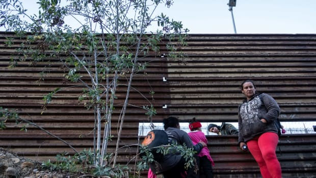 Honduran migrants look through the U.S.-Mexico border fence in Tijuana, Mexico on December 15th, 2018. Former Attorney Jeff Sessions issued an interim decision in June in which he ruled that the violence survivors did not merit asylum.