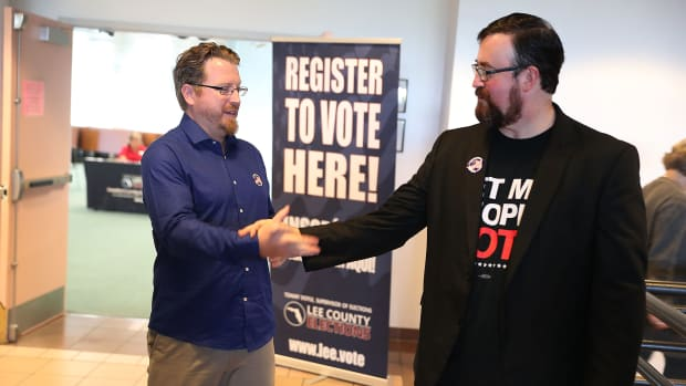Lance Wissinger (left) and Neil Volz shake hands after turning in their voter registration forms at the Lee County Supervisor of Elections office on January 8th, 2019, in Fort Myers, Florida. Wissinger and Volz, both with felony records, became able to vote for the first time after a new constitutional amendment took effect.