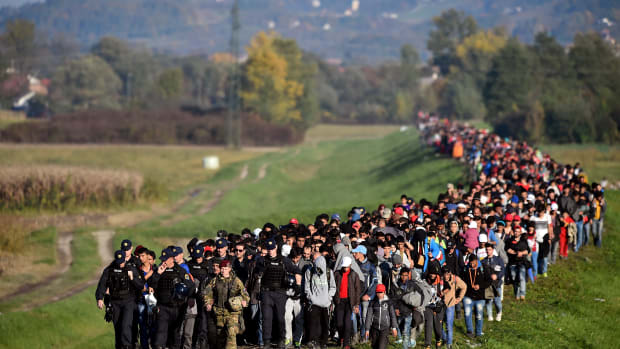 Migrants are escorted through fields by police and the army as they are walked from the village of Rigonce to Brezice refugee camp on October 24th, 2015, in Rigonce, Slovenia.