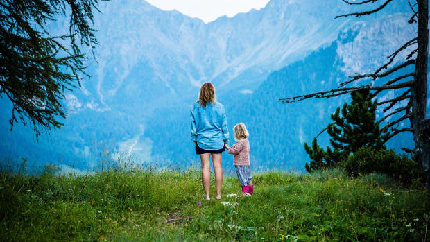 Mother and child in nature; mountain view with trees.