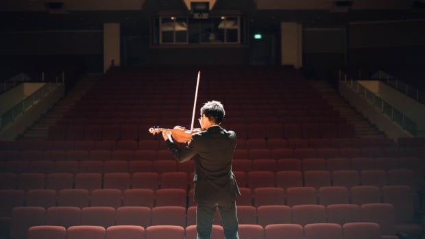 A man plays the violin in a theater.