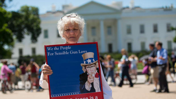 A woman walks with a sign to protest gun violence and call for sensible gun laws outside the White House in June of 2016. One advocacy group, Cure Violence, approaches violence as a public-health issue, and has seen success reducing gun violence.