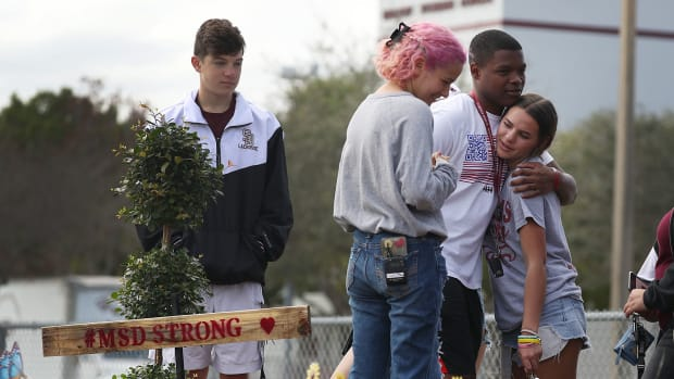 Students from Marjory Stoneman Douglas High School spend time together at a memorial set up outside the school on February 14th, 2019, in Parkland, Florida. A year ago on February 14th, 14 students and three staff members were killed during a mass shooting. For the one-year anniversary of the shooting, Pacific Standard took a look at federal, local, and non-governmental gun-violence proposals.