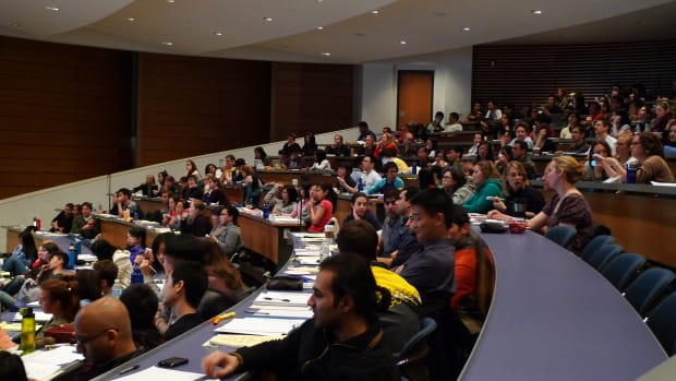 Students sit in a college lecture hall.