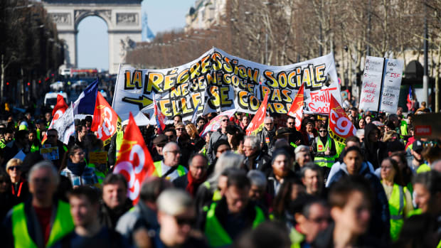 Gilets jaunes (yellow vest) protesters march down the Champs-Elysees in Paris, France, on February 17th, 2019. The yellow vests movement began in November after French President Emmanuel Macron announced impending fuel taxes, which many rural French citizens said they could not afford, and calls for government tax reforms to address the high cost of living and for Macron's resignation.