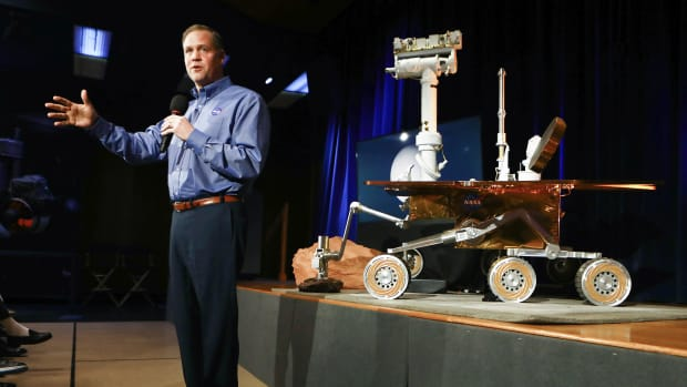 NASA Administrator Jim Bridenstine in front of a model of the Opportunity rover