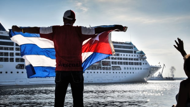 A man waves a Cuban flag at the Malecon waterfront as the first U.S.-to-Cuba cruise ship to arrive in the island nation in decades glides into the port of Havana, on May 2nd, 2016.