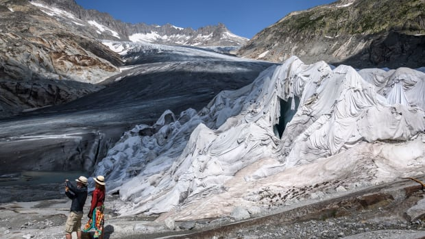 A couple take a photograph next to a part of the Rhone Glacier, covered with insulating foam to prevent it from melting, near Gletsch, Switzerland, on August 3rd, 2018, as a heatwave sweeps across northern Europe.