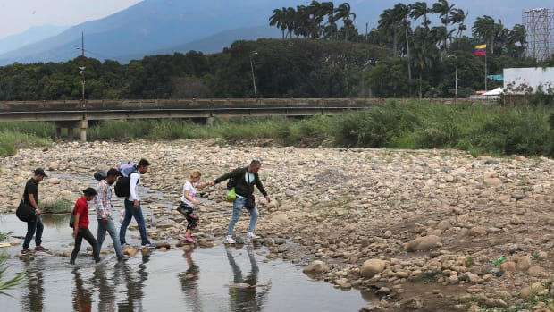 People cross through the low waters of the Táchira River near the Simón Bolívar international bridge, which connects Cúcuta, Colombia, with the Venezuelan town of San Antonio del Táchira, after the closure of the border bridge on February 27th, 2019, in Cúcuta, Colombia. Many people are making the trek through the river from Venezuela to get supplies or to escape the conditions in their country.