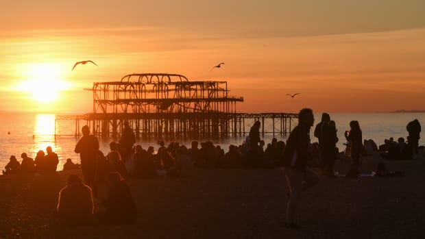 People enjoy the sunset on the beach by the derelict West Pier on February 25th, 2019, in Brighton, England.