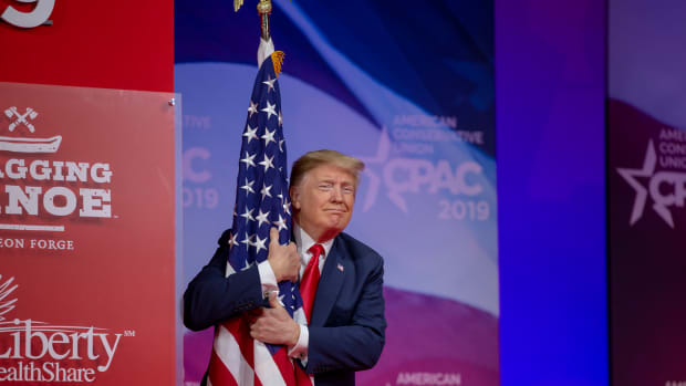President Donald Trump hugs the United States flag during CPAC 2019.