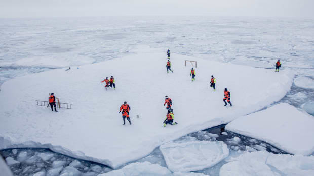 The crew of patrol vessel KV Svalbard and scientists from the Norwegian Institute of Marine Research play football on a floe of offshore ice on March 22nd, 2018, in the sea around Greenland, while two armed guards keep watch for polar bears.