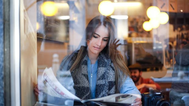Woman reading newspaper news media