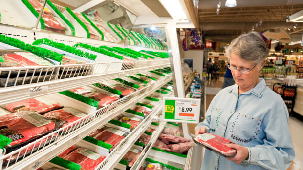 A shopper examines a package of meat in a grocery store.