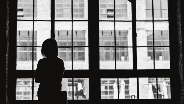 A woman in silhouette gazes out a window (and is a neutral image for stories about stuff like depression)