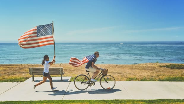 man woman american flag beach  water ocean